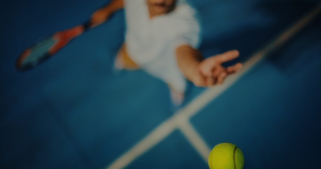 man serving on the baseline on a hard court - Australian Open Packages
