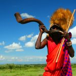 African Tours - Traditionally dressed African Man playing musical instrument